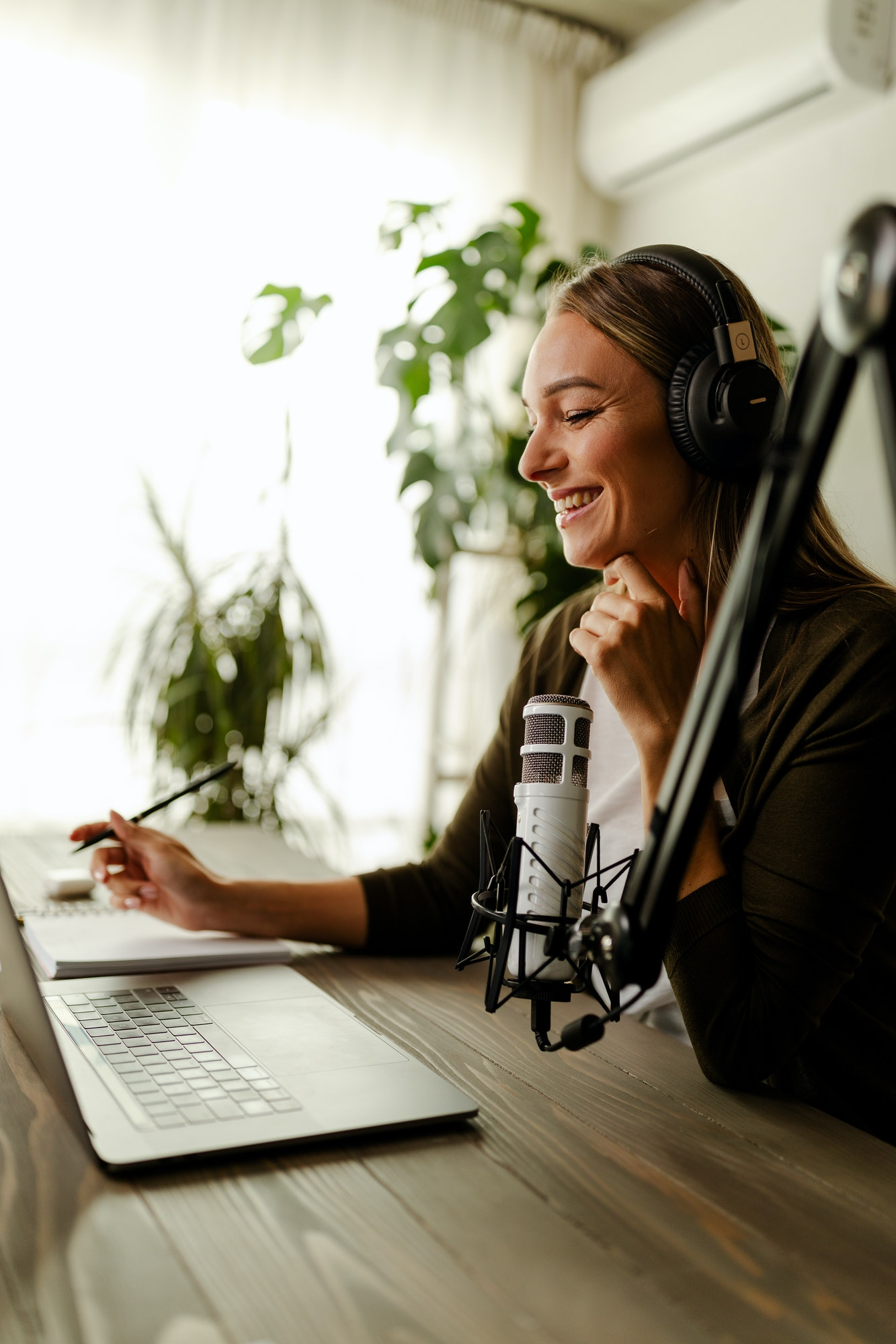 Young woman recording podcast using microphone. Radio host working from home.
